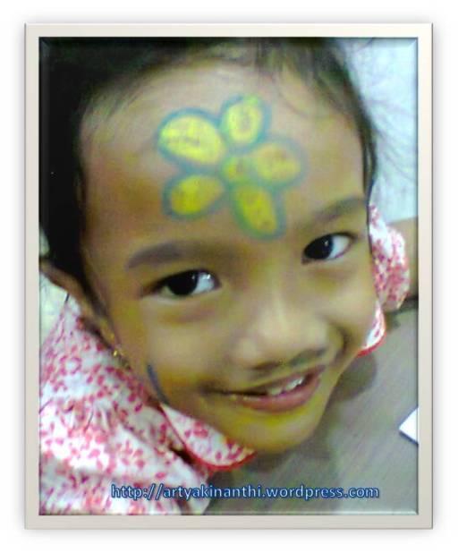 Kinan dengan Face decoration ala Bunga, yang ini dibantu emaknya yang kasih kerangka bunga-nya kinan yang mewarnai kuningnya Happy banget nieh anak